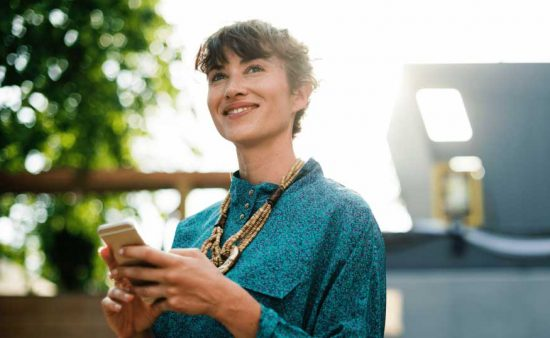 small image of happy looking woman holding phone